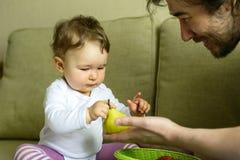 Le bébé mignon joue avec des fruits avec son père à la maison images stock