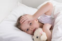 Le bébé, ne veut pas sortir du lit, sa tête blesse image libre de droits