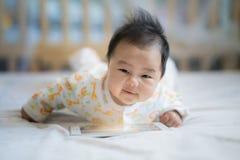 Le bébé nouveau-né écoutent chanson de téléphone intelligent Image stock