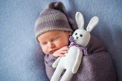 Le bébé nouveau-né de sommeil minuscule couvert de pourpre riche a coloré l'enveloppe photos stock