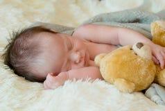 le bébé nouveau-né dort avec un ours de nounours de jouet Photo stock