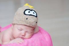 Le bébé nouveau-né heureux mignon dans le dragon a tricoté le chapeau dormant sur la couverture rose Portrait infantile de sommei Photographie stock