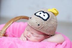 Le bébé nouveau-né heureux mignon dans le dragon a tricoté le chapeau dormant sur la couverture rose Portrait infantile de sommei Photos libres de droits