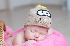 Le bébé nouveau-né heureux mignon dans le dragon a tricoté le chapeau dormant sur la couverture rose Portrait infantile de sommei Image libre de droits