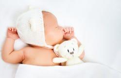Le bébé nouveau-né mignon dans le chapeau d'ours dort avec l'ours de nounours de jouet Photos stock