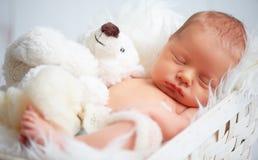 Le bébé nouveau-né mignon dort avec l'ours de nounours de jouet Photo stock