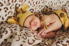 Le bébé nouveau-né mignon dort dans une girafe de chapeau sur le backgro repéré images stock