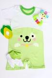 Le bébé nouveau-né a modelé la combinaison avec la photo d'un visage de chien, des butins de tricots, du hochet et du teether Image stock