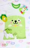 Le bébé nouveau-né a modelé la combinaison avec la photo d'un visage de chien, des butins de tricots, du hochet et du teether Photographie stock libre de droits