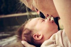 Le bébé nouveau-né sur des mains de mère avec émotion franche symbolisent l'amour et la garde d'enfants Photos stock