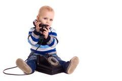 Le bébé parle par le téléphone de cru images stock