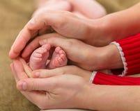 Le bébé paye dans des mains de parents Photos stock