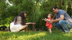 Le bébé prend des premières étapes avec l'aide de la maman et du papa sur l'herbe de pelouse banque de vidéos
