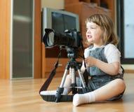 Le bébé prend la photo avec l'appareil-photo et le trépied Photos stock
