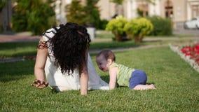Le bébé prend les premières étapes Pièces de mère avec l'enfant banque de vidéos