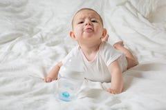Le bébé radote et fait ses dents Il se trouve sur un lit blanc et tire ses mains dans une bouteille de l'eau Enfant sombre et vil photographie stock libre de droits