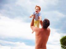 Le bébé ravi avec bonheur est jeté par le papa dans le ciel Photos libres de droits