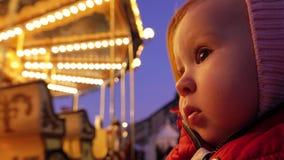 Le bébé regarde le beau carrousel lumineux le soir photo stock