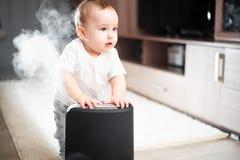 Le bébé regarde l'humidificateur Humidité dans le concept sain à la maison d'air images libres de droits
