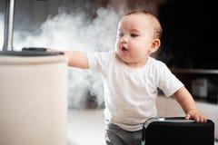 Le bébé regarde l'humidificateur Humidité dans le concept sain à la maison d'air photo libre de droits