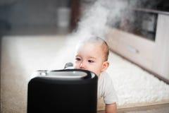 Le bébé regarde l'humidificateur Humidité dans le concept sain à la maison d'air image libre de droits