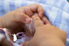 Le bébé remet attraper une tétine images stock