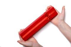 Le bébé remet juger un boîte-cadeau rouge d'isolement sur un fond blanc Vue supérieure Image stock