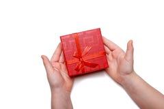 Le bébé remet juger un boîte-cadeau rouge d'isolement sur un fond blanc Vue supérieure Image libre de droits