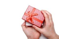 Le bébé remet juger un boîte-cadeau rouge d'isolement sur un fond blanc Vue supérieure Images stock