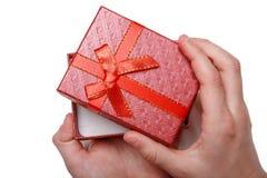 Le bébé remet juger un boîte-cadeau rouge d'isolement sur un fond blanc Vue supérieure Photos stock