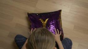 Le bébé remet la forme de coeur de dessin sur l'oreiller décoratif avec le tissu de paillette Vue supérieure banque de vidéos