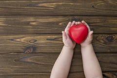 Le bébé remet tenir un coeur rouge sur un fond en bois de texture photographie stock