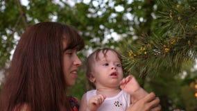 Le bébé s'asseyant sur des bras de mère regarde des aiguilles sur le pin clips vidéos