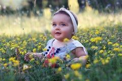 Le bébé s'asseyant sur l'herbe avec le pissenlit fleurit Photographie stock