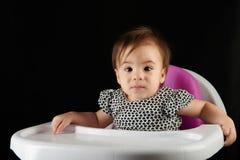 Le bébé s'asseyent sur manger la table de chaise images stock