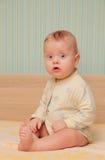 Le bébé s'asseyent sur un berceau Photo stock