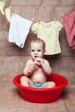 Le bébé s'assied dans un bassin image libre de droits