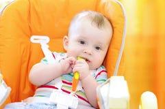 Le bébé s'assied sur la chaise et tient la cuillère Image libre de droits