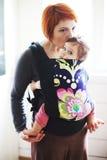 Le bébé s'est tenu par sa mère dans une bride Image libre de droits