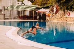 Le bébé sautant dans la piscine image libre de droits