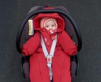 Le bébé se situe dans un siège de voiture du ` s d'enfants Images stock