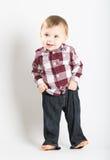 Le bébé se tient dans la flanelle et des jeans tirant vers le haut le pantalon Photo libre de droits
