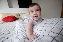 Le bébé se trouvant sur ses parents enfoncent avec l'expression drôle Images libres de droits