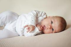 Le bébé se trouve sur le plaid lumineux dans des pyjamas blancs Image libre de droits