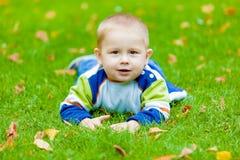 Le bébé se trouve sur le pré Photographie stock