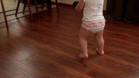 Le bébé tient nu-pieds une colonne et des promenades de musique sur le plancher dans le mouvement lent banque de vidéos