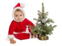 Le bébé triste en Santa Claus vêtx avec l'arbre de Noël Photographie stock