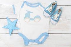 Le bébé vêtx pour le petit garçon sur le fond en bois Configuration plate Photos libres de droits