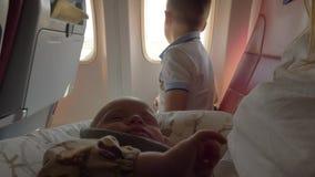 Le bébé voyageant en avion avec la famille se réveille banque de vidéos