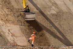 Le bêcheur fonctionne au nouveau site de construction de routes Image stock